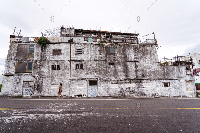 Unrecognizable female walking along pavement with shabby abandoned building located against gray sky on East Coast