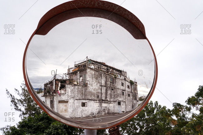 Shabby abandoned building reflecting in convex mirror located on road on East Coast