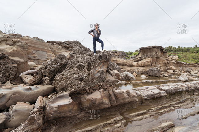 Traveling female standing on rough rocky formation in mountainous area while admiring landscape on East Coast while taking picture with smartphone