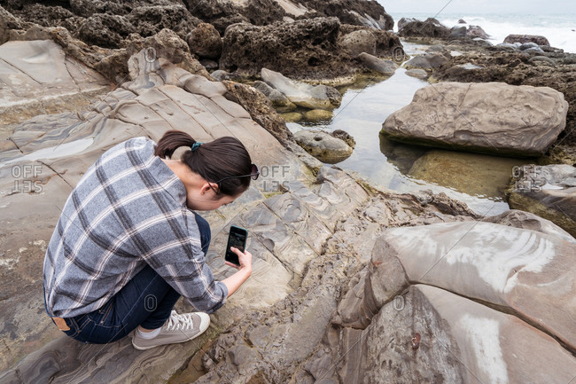 High angle of woman with smartphone taking photo of rocky shore near sea during summer travel on East Coast