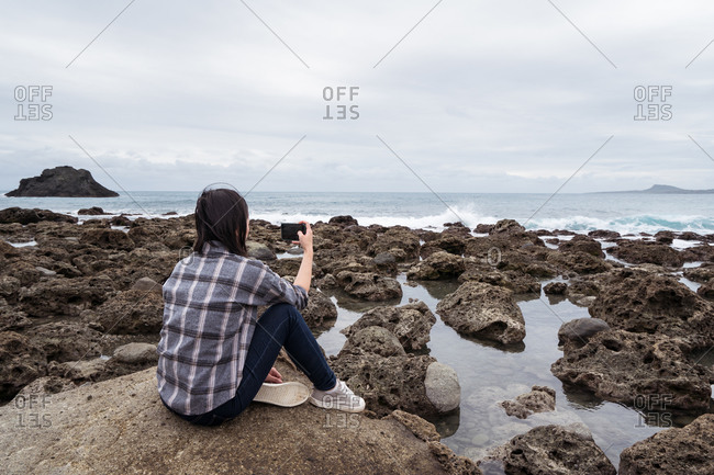 Back view of unrecognizable female tourist in casual wear sitting on rock and taking photo of seascape while enjoying summer vacation on East Coast