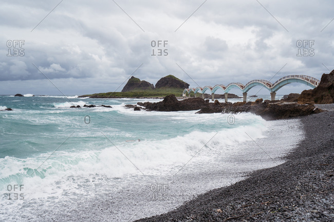 Scenic view of old bridge leading through stormy sea to island on East Coast in overcast weather