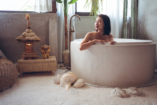 Happy young Asian woman enjoying bath time in bathtub in hotel room with traditional oriental decor while spending holidays in Taiwan