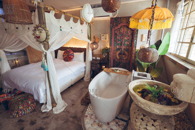 Cozy bed with canopy and white bathtub located in hotel room with traditional oriental furniture and decorations in Taiwan
