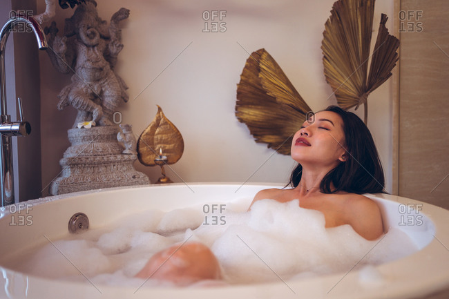Relaxed young Asian female sitting in small round bathtub with foam and enjoying bath procedure in spa salon with oriental decor