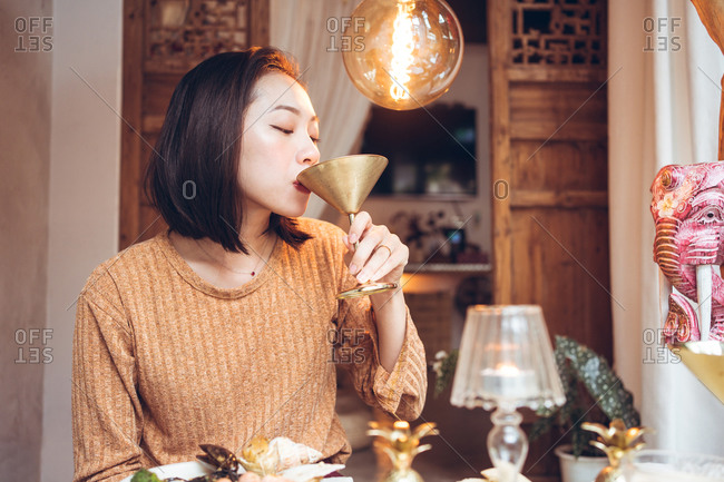 Young Asian female drinking alcohol cocktail from metal goblet while having dinner in hotel room in Taiwan