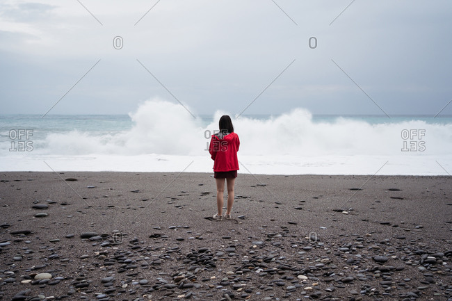 Back view of anonymous female traveler standing on wet beach and admiring view of stormy sea on cloudy day in Hualien City
