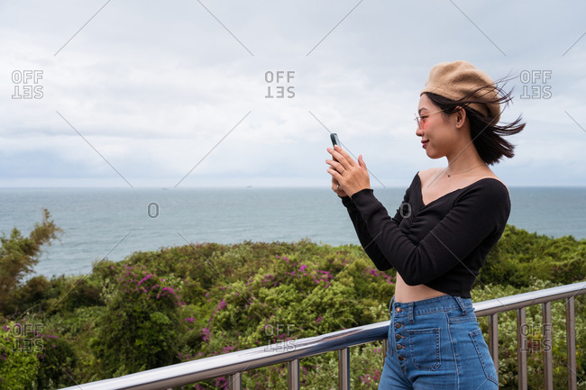 Side view of happy young Asian female tourist in casual outfit and beret capturing picture of sea with mobile phone while standing on viewpoint near green trees in cloudy windy day in Taiwan