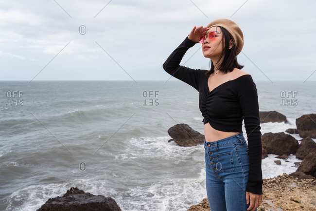 Side view of young Asian female in casual clothes standing on rocky coast near stormy sea and looking away while observing seascape