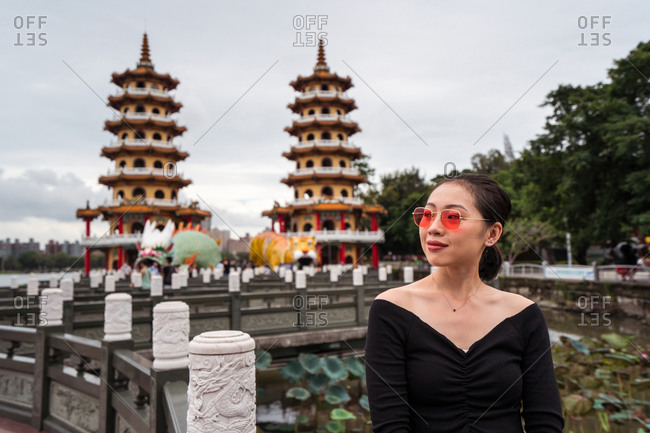Young Asian female tourist standing on stone bridge against buildings of Buddhist Dragon and Tiger pagodas while visiting Kaohsiung city in Taiwan