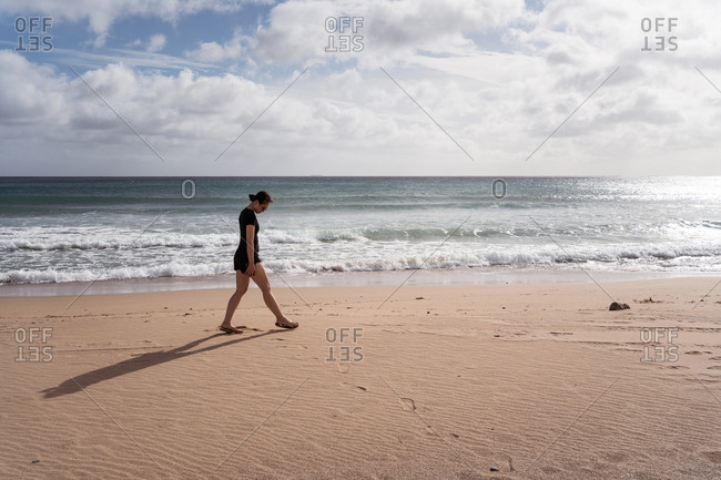 Full body side view of unrecognizable lonely female walking on sandy shore against waving sea in sunny day with cloudy sky