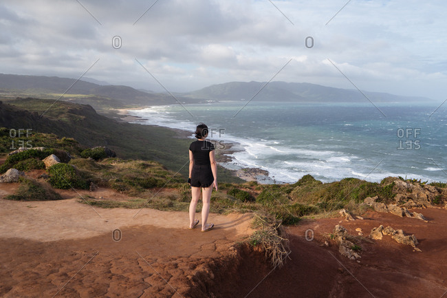 Full body back view of unrecognizable female traveler in black clothes standing alone on hilly shore against waving sea in overcast weather and contemplating nature