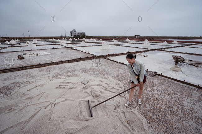 Full body of young Asian female traveler with shovel getting experience of work in salt factory while visiting Jingzaijiao Tile paved Salt Fields in Taiwan