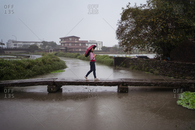 Side view of female with umbrella walking along wooden footbridge while enjoying solitude on rainy day in Yilan county and looking away
