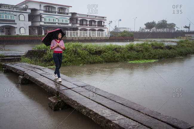 Female with umbrella walking along wooden footbridge while enjoying solitude on rainy day in Yilan county and looking away