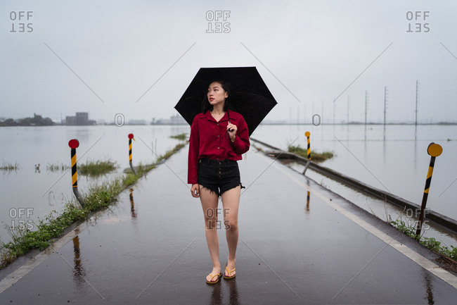 Melancholic female with umbrella walking barefoot along wet empty road on rainy day under cloudy sky in Yilan County