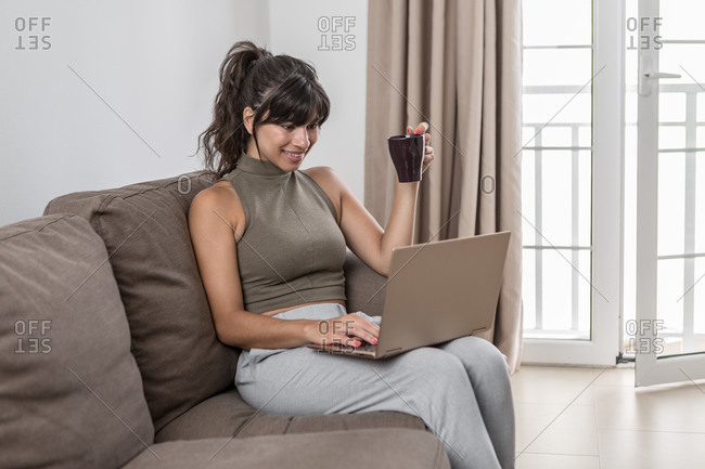 Glad female wearing casual clothing sitting on couch with modern netbook while drinking hot beverage in a mug at light living room