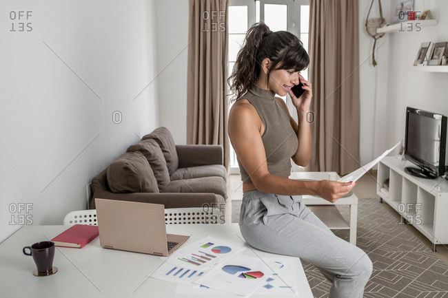 From above side view of positive female in formal wear sitting on desk with sheet of paper and talking on mobile phone in office