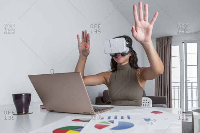 Positive smiling female with arms raised using VR headset while sitting at table with contemporary laptop and papers