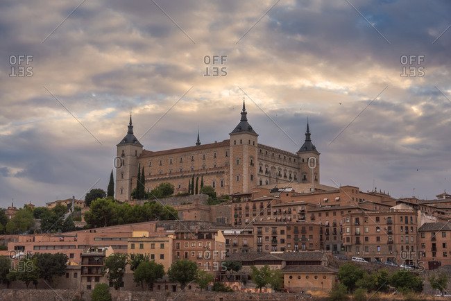 Aerial view of old city with historic buildings and stone castle on hill against cloudy sky during sunset in Toledo, Spain
