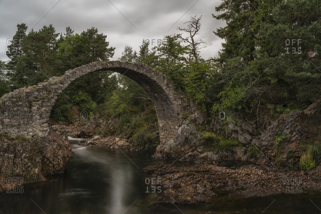 Scenery of Old Pack Horse Bridge over calm river under cloudy sky in Scotland