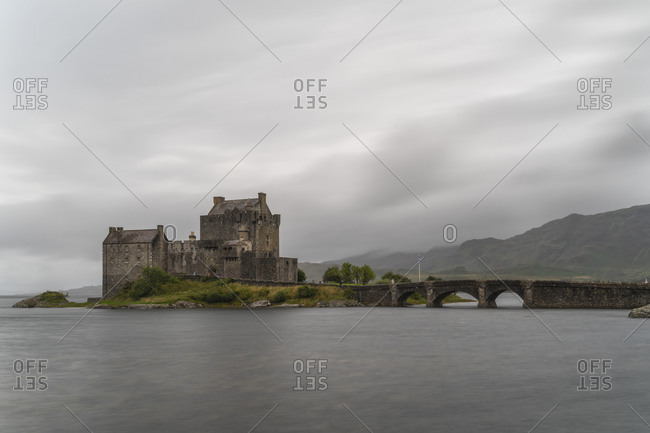 Ancient Eilean Donan Castle with old stone bridge on overcast day in mountainous area in Scotland