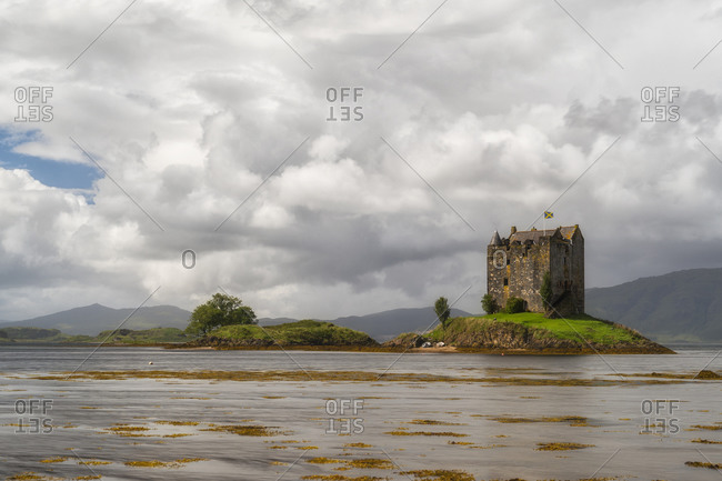 Distant view of magnificent ancient Castle Stalker located near calm lake in Scotland