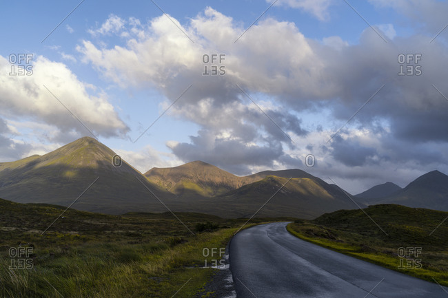 Scenic view of asphalt roadway in highland area with mountain range illuminated by sunlight in Scotland