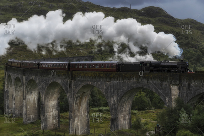 Old fashioned steam train riding along Glenfinnan Viaduct located in mountains on cloudy day in Scotland