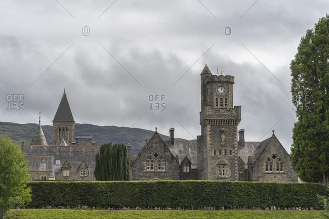 Exterior of stone aged castle surrounded by green trees and located in mountains in Scotland