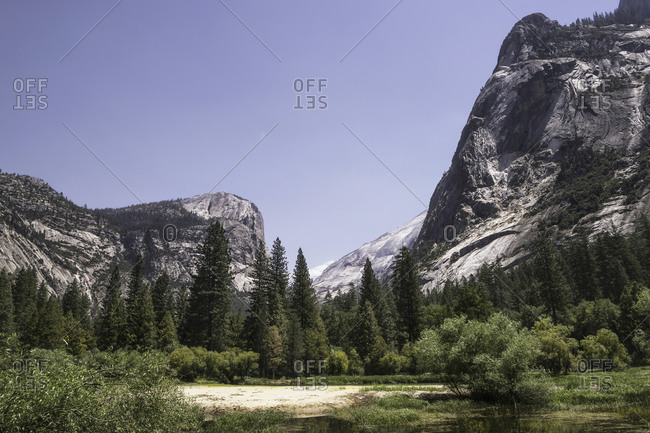 Magnificent landscape of rocky mountain range and calm river located in Yosemite National Park on sunny day