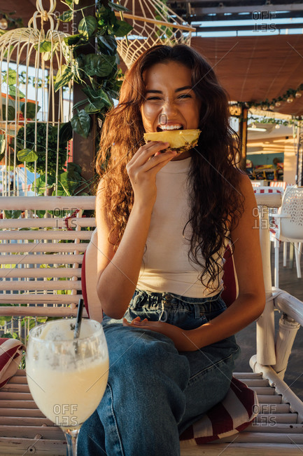 Playful young female making grimace and biting fresh pineapple while chilling in outdoor cafe in summer evening