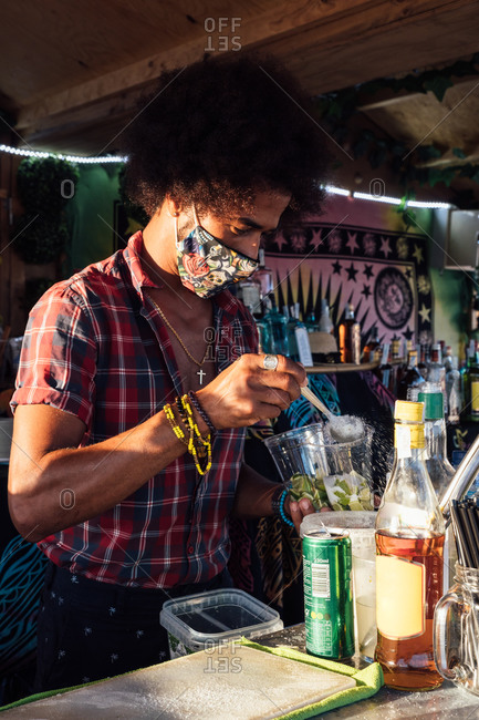 African American male barkeeper in protective mask garnishing cocktail with slice of fresh lime while preparing drink at counter of beach bar
