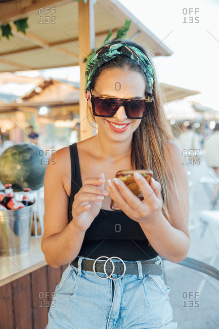 Cheerful young female in stylish summer clothes and sunglasses reading message on smartphone while resting in tropical bar in summer day
