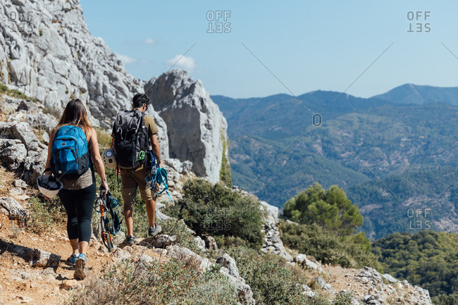 Full body back view of unrecognizable man and woman with backpacks and safety equipment walking on trail on rocky mountain slope