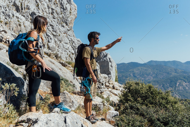 Side view of man and woman with backpacks and safety equipment standing on trail admiring rocky mountain slope