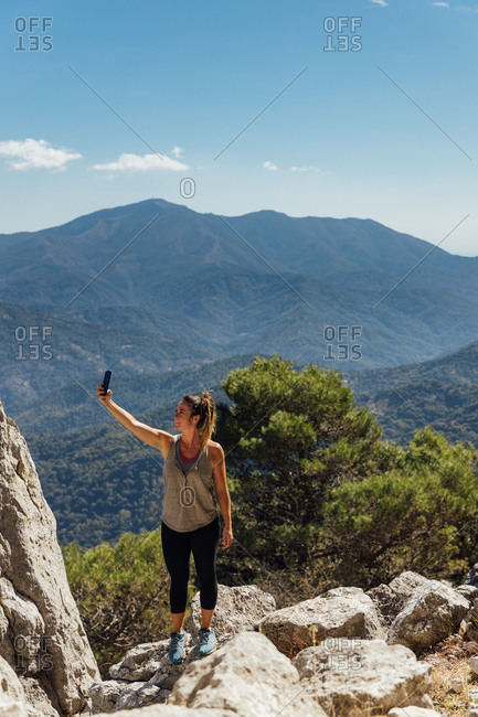 Full body of active female explorer standing on rocky mountain top and taking selfie on smartphone against picturesque mountainous landscape in summer day