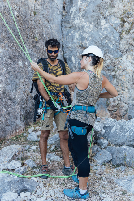 Fearless active couple in safety harnesses preparing gear for ascending rocky mountain slope while practicing climbing in nature