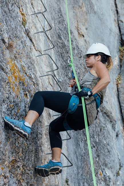 From below side view of determined active female climber in safety harness and helmet using belay device while practicing rappelling technique in mountains