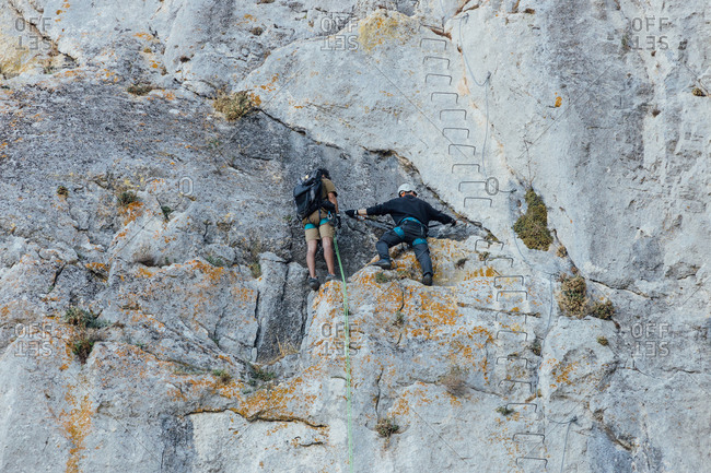 From below back view of brave unrecognizable climbers ascending rough steep rocky slope while practicing climbing together in mountainous terrain