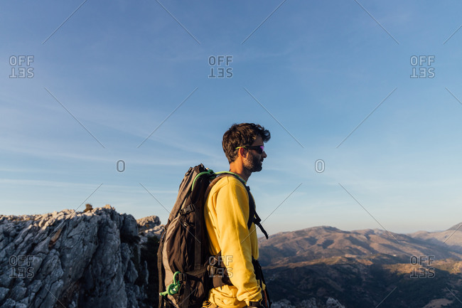 Side view of lonely unrecognizable male explorer with backpack standing on top of rough rocky mountain and enjoying freedom while hiking through highlands at sunset