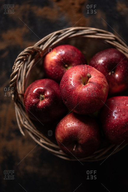 Top view of pile of wet red apples placed in wicker basket on rustic table