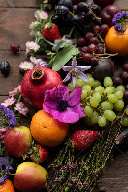 From above of assorted ripe fruits and fresh vivid flowers arranged on wooden table in countryside