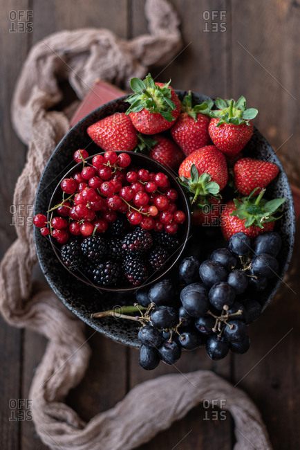 Top view of bowl with various healthy fruits and berries placed on table near old towel in rustic kitchen