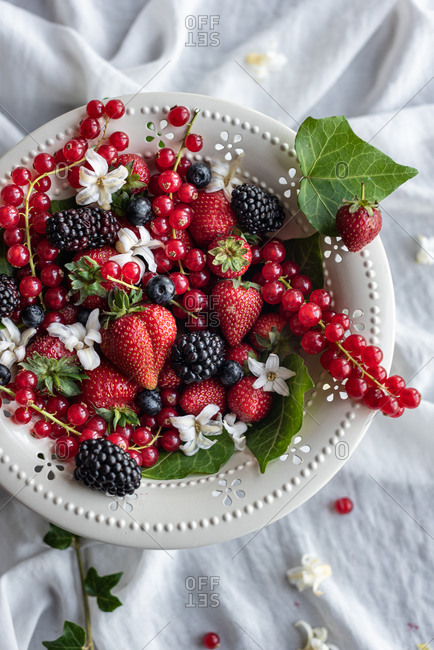 Top view of assorted fresh berries placed in plate on table with white tablecloth in rustic kitchen