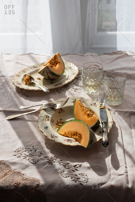 From above of slices of sweet melon served in plate on table in countryside on sunny day