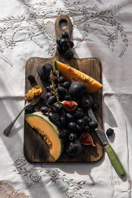 Top view of delicious sweet fruits placed on old wooden chopping board on table in cozy kitchen