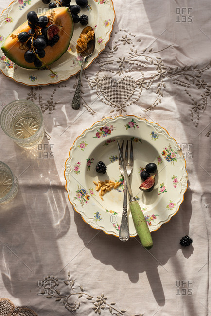 From above of empty plate from fruits arranged on table with ripe melon and grapes in rustic kitchen