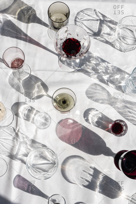 From above of glasses with various alcohol beverages casting shadows and flares on white table