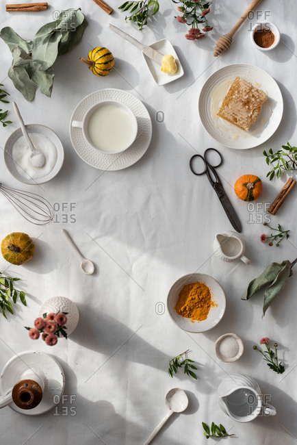 Top view of layout of cup of warm milk and natural honey placed near bowl of sugar and butter on table with spices and dried plants